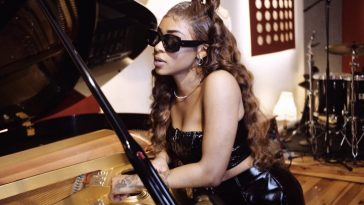 "Still from ""Liar Liar"" music video where Relley C is wearing sunglasses and leaning against a piano."