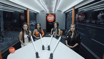 "4th Impact sitting around a table with microphones inside the Wish 107.5 Bus singing their song ""K(NO)W MORE""."