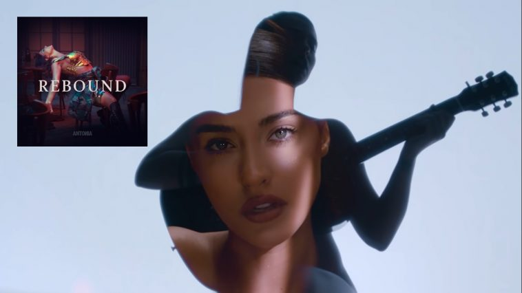 """Still from """"Rebound"""" music video which sees Antonia topless holding a guitar in front of her whilst a different scene from the video is projected onto her body. The single artwork also appears in the left-top corner which sees Antonia wearing a gold top leaning back on to a table within a bar setting."""