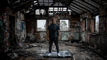 "Still from the ""Demons"" music video which sees Sam Callahan standing on top of a smashed TV within an abandoned building. He is wearing a black t-shirt, a black gilet, black skinny jeans and white trainers."