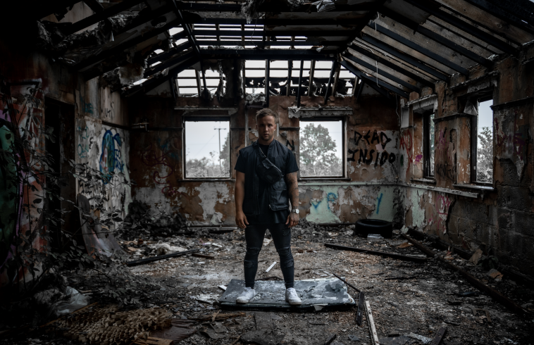 """Still from the """"Demons"""" music video which sees Sam Callahan standing on top of a smashed TV within an abandoned building. He is wearing a black t-shirt, a black gilet, black skinny jeans and white trainers."""