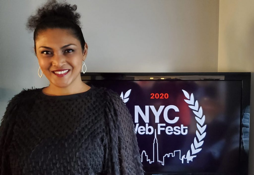 Lauren Atkins, founder of the 2020 NYC Web Fest, wearing a black jumper, standing in front of a television with the NYC Web Fest 2020 logo on it