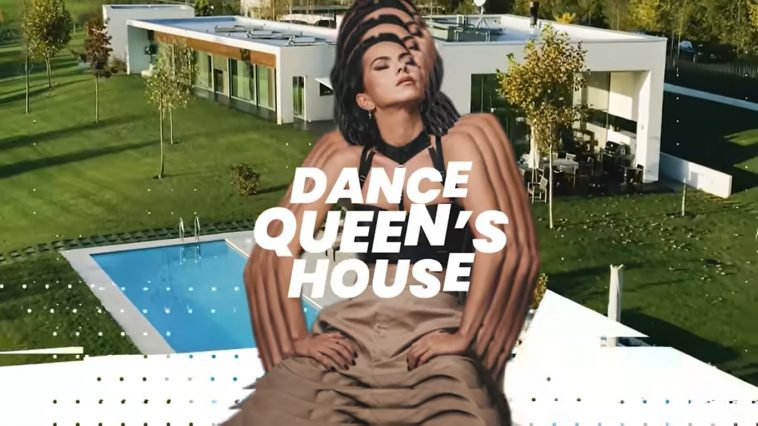 """INNA posing with hands on hips wearing grey/brown trousers and a black bra with her head tilted up and to the right. In the background there is the pool and the house, and the words """"Dance Queen's House"""" in white across INNA's chest."""