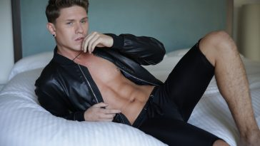 Press photo for Joey Suarez who is lying on a bed wearing some black shorts and an open leather jacket.